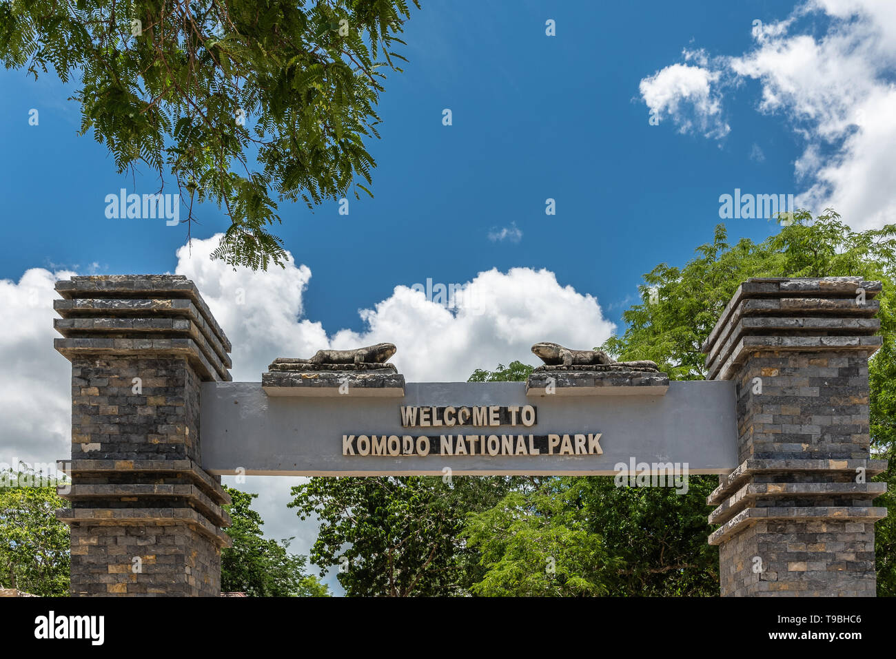 Komodo Island, Indonesia - February 24, 2019: Komodo National Park. Sign on top of brown brick gate into the National Reserve. Green foliage under blu - Stock Image
