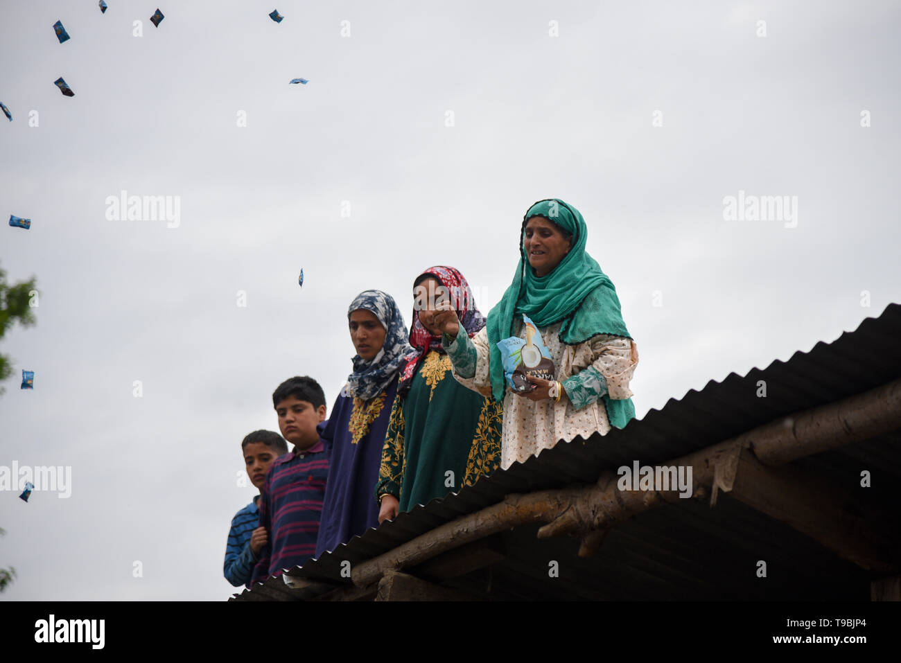 A Kashmiri woman seen throwing candies during the funeral procession of slain JeM Militant Naseer Ahmed Pandit during his funeral at his residence in Pulwama, South of Srinagar. Three militants, an army man and a civilian were killed in a fierce gunfight that broke out in Dalipora area of Pulwama town in south Kashmir on Thursday morning. - Stock Image