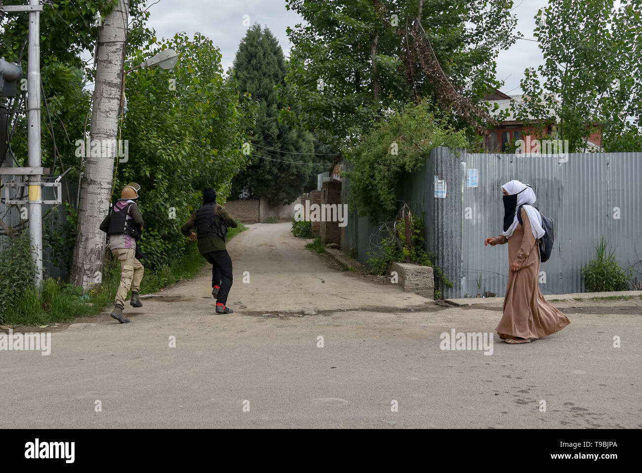 A policeman seen chasing kashmiri Protester during the clashes in Pulwama, South of Srinagar. Three militants, an army man and a civilian were killed in a fierce gunfight that broke out in Dalipora area of Pulwama town in south Kashmir on Thursday morning. - Stock Image