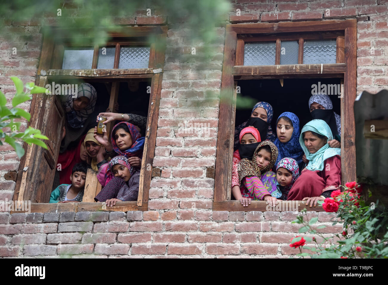 Kashmiri villagers seen watching the funeral procession of slain JeM Militant Naseer Ahmed Pandit at his residence in Pulwama, South of Srinagar. Three militants, an army man and a civilian were killed in a fierce gunfight that broke out in Dalipora area of Pulwama town in south Kashmir on Thursday morning. - Stock Image