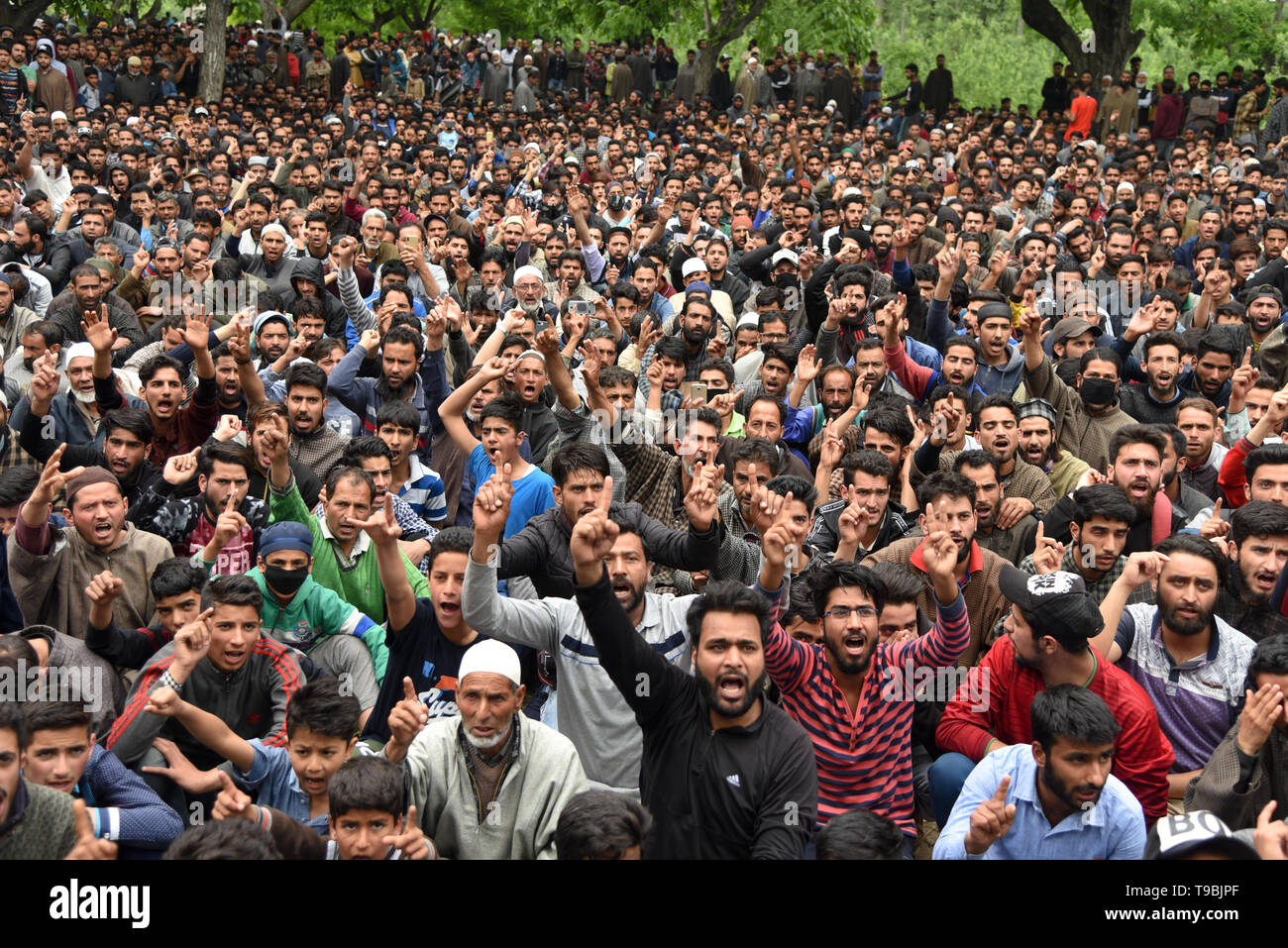 Kashmiri Muslim villagers seen gathered while chanting slogans during the funeral procession of slain JeM Militant Naseer Ahmed Pandit at his residence in Pulwama, South of Srinagar. Three militants, an army man and a civilian were killed in a fierce gunfight that broke out in Dalipora area of Pulwama town in south Kashmir on Thursday morning. - Stock Image