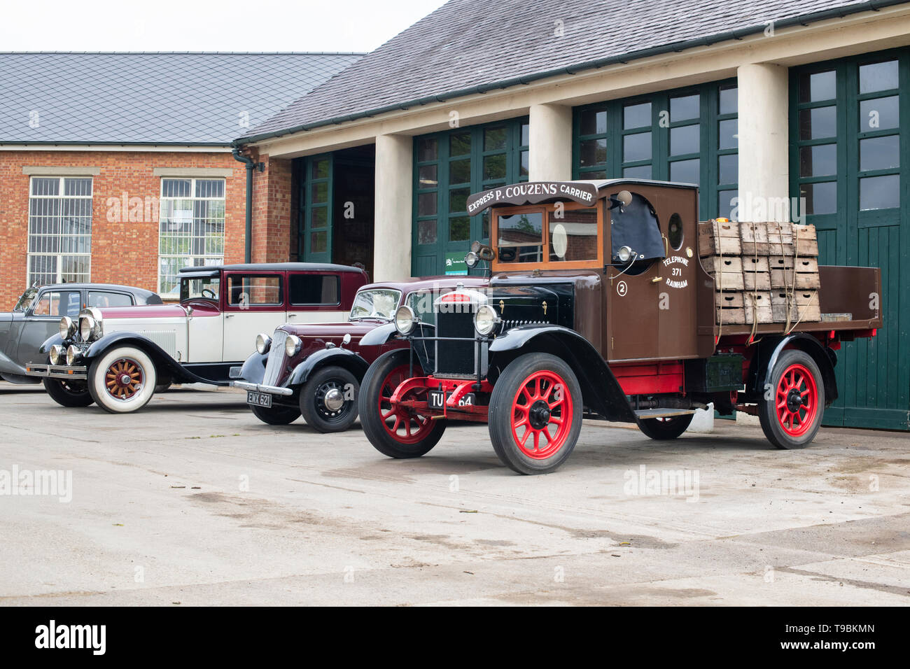 Vintage lorry and cars outside a garage at Bicester Heritage Centre 'Drive It Day'.  Bicester, Oxfordshire, England. - Stock Image