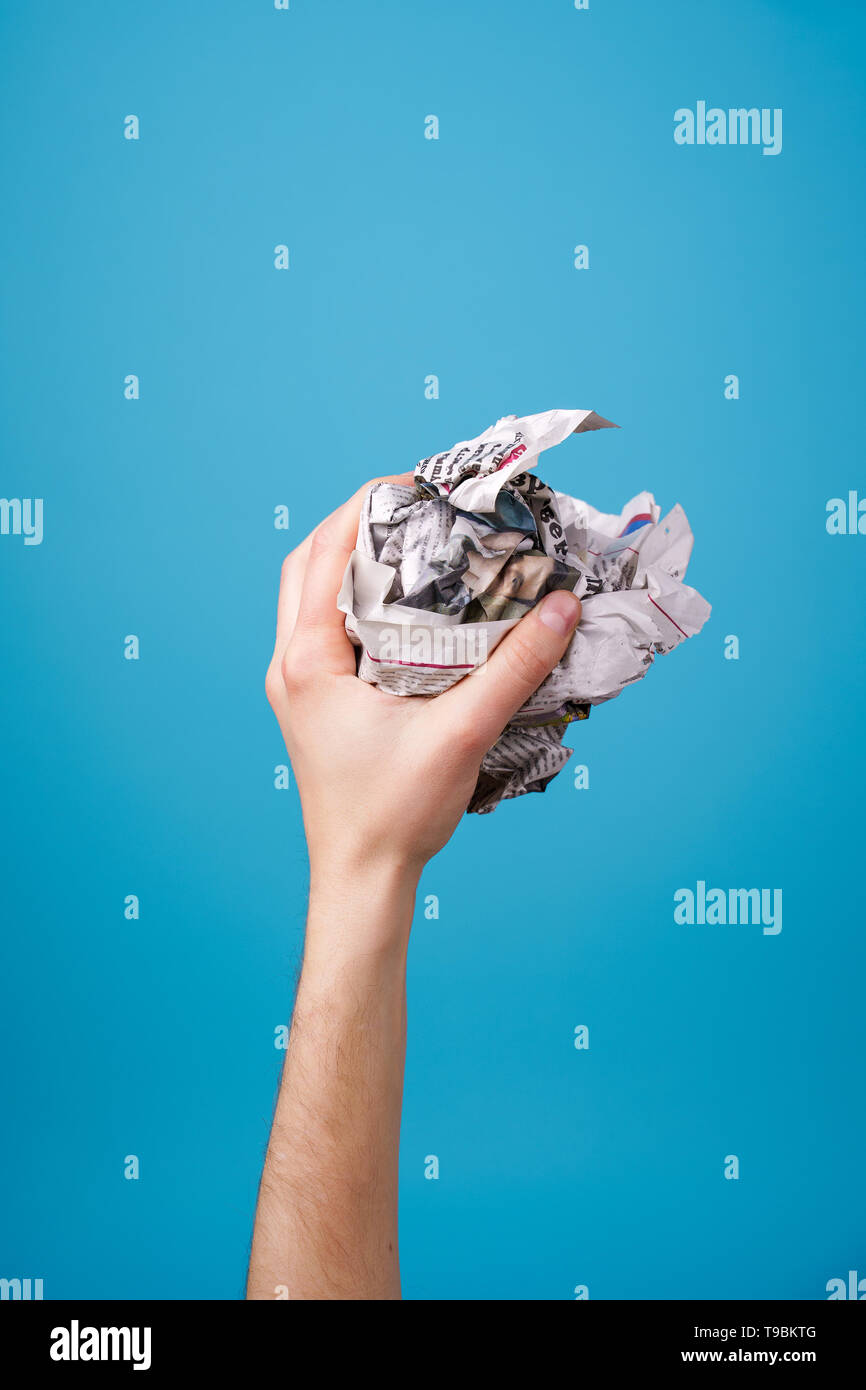 hand with crumpled newspaper. - Stock Image