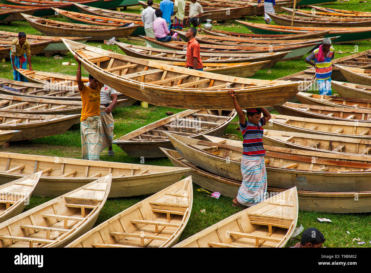 Craftsmen seen carrying a boat among hundreds of little wooden boats displayed for sale at a market as locals prepare for monsoon season.  Dozens flock from miles around to buy their own boat at a market in Manikganj, Bangladesh, so as to be prepared for floods which can strike at any time. After heavy rainfall it is common for river banks to burst, submerging nearby towns and villages. This means cars and buses become redundant and people are forced to travel by boat. Each of the wooden boats and oars are hand-made by local craftsmen and can be bought for as little as 1700 Bangladeshi Taka -  - Stock Image