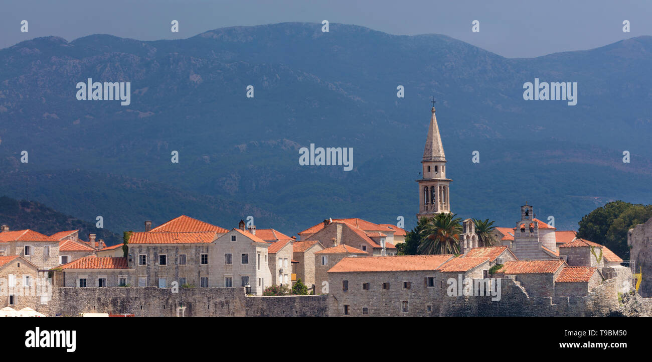 Red-tiled roofs of the city of Budva against the mountains and sky. Montenegro. - Stock Image