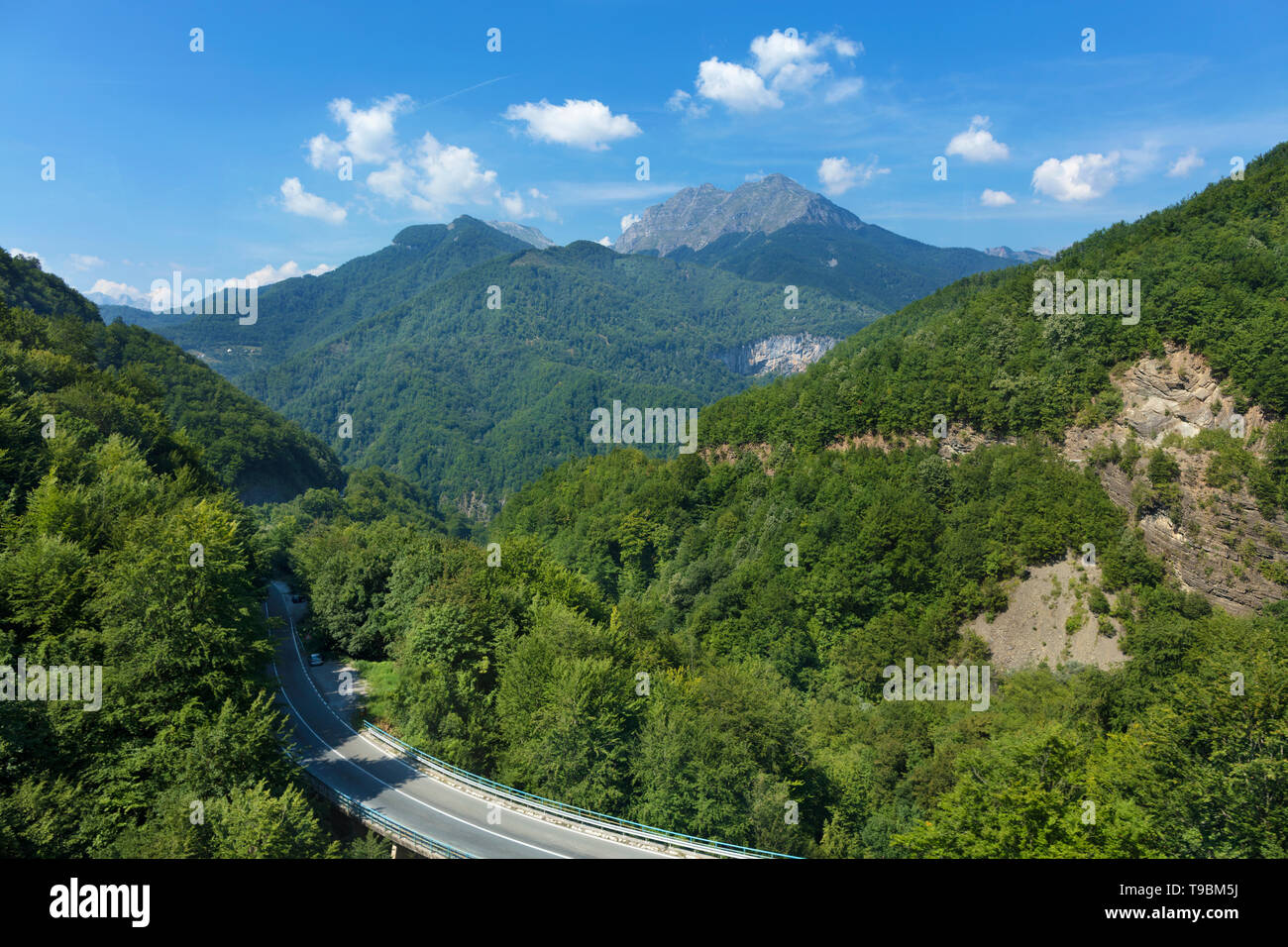 Aerial view of the greenery of the mountain massifs of Montenegro and the road, serpentine winding among the mountains. Stock Photo