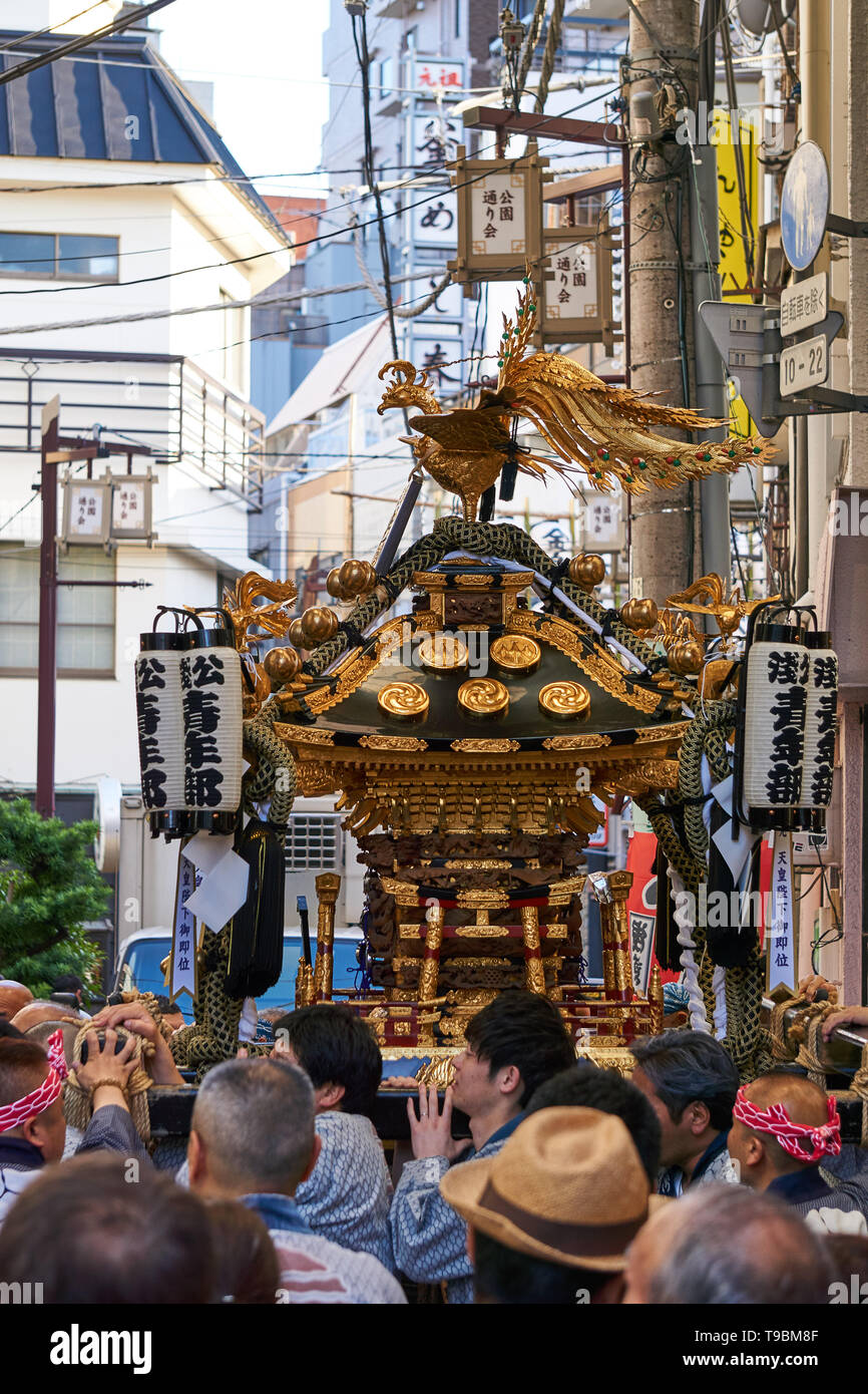 Japanese men carry or hoist up a mikoshi (omikoshi, portable shrine)  on the street during the Sanja Matsuri Festival, in Asakusa Japan. - Stock Image