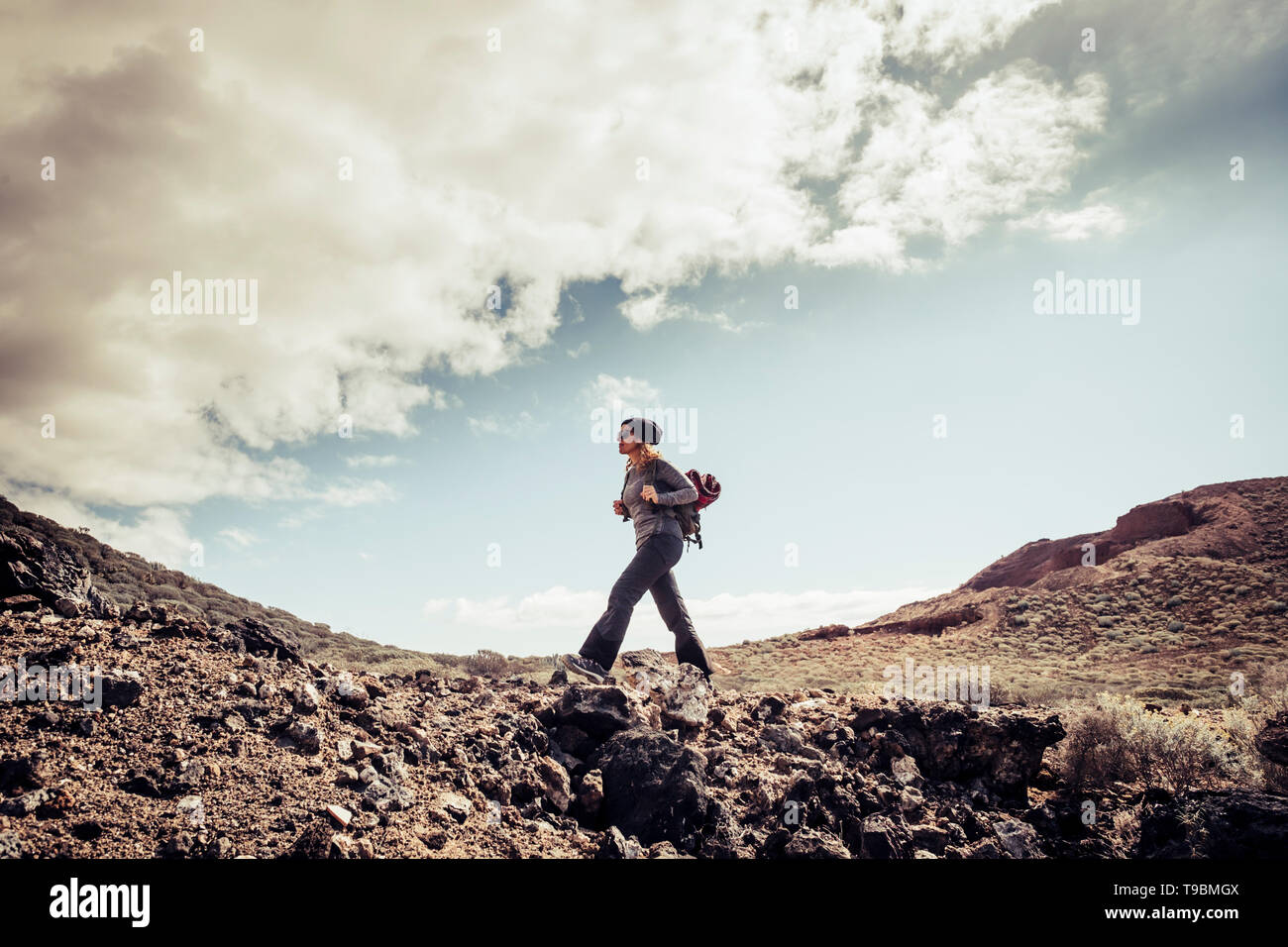 Young active people caucasian blonde woman in trekking outdoor leisure activity lifestyle in the arid mountains for healhty sport day - adventure and  - Stock Image