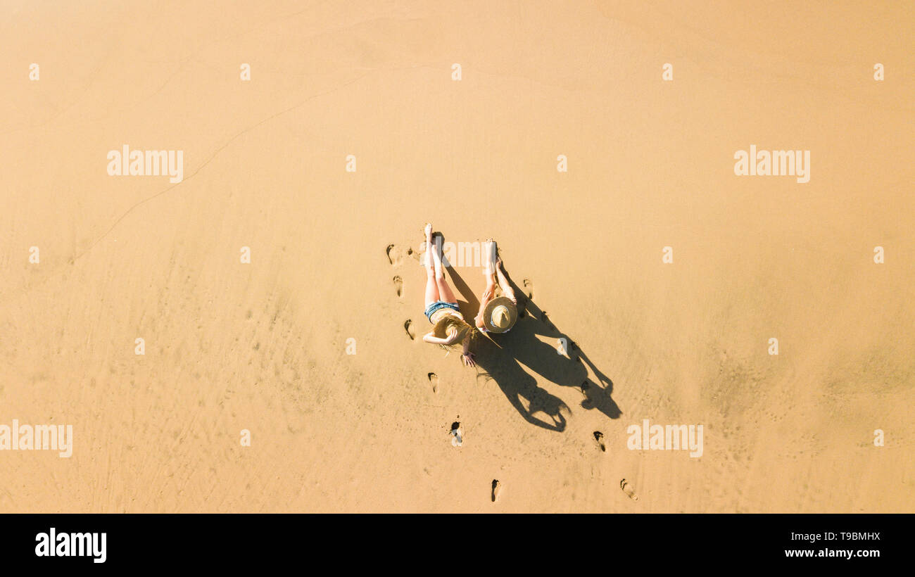 Aerial view with couple of beautiful young girls enjoyimg the beach like tourists in summer holiday vacation leisure activity - nice shadow on the flo Stock Photo