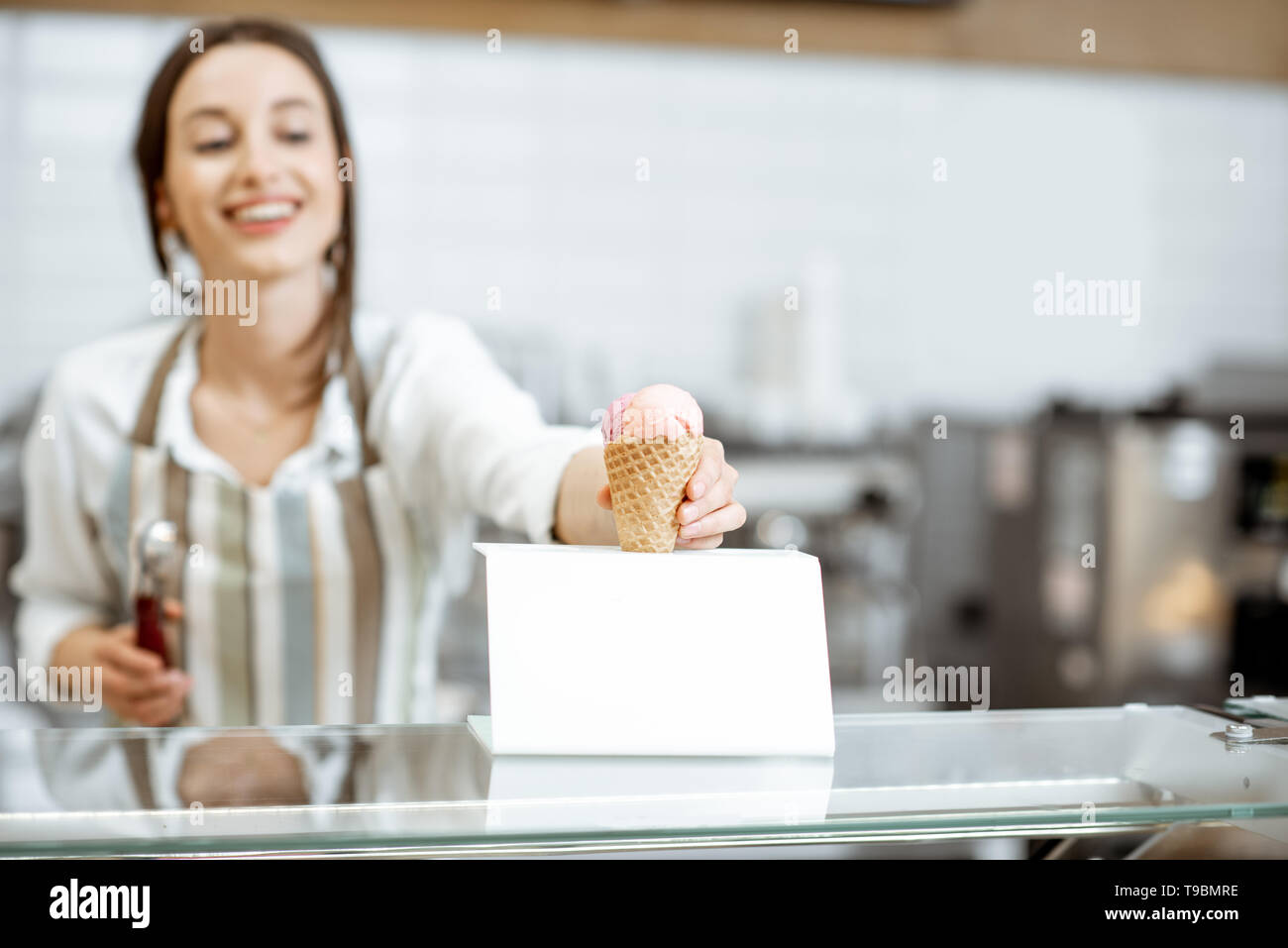 Young and happy saleswoman in apron making ice cream at the counter of the modern pastry shop indoors Stock Photo