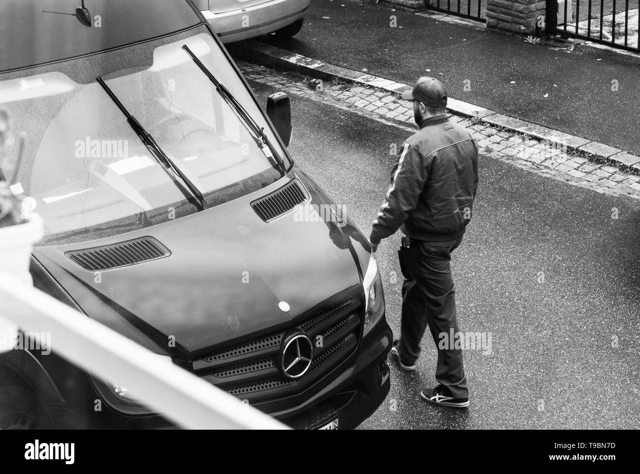 Paris, France - Apr 10, 2019: Black and white image of elevated view of UPS employee walking on the street toward his brown van after delivering a parcel Stock Photo