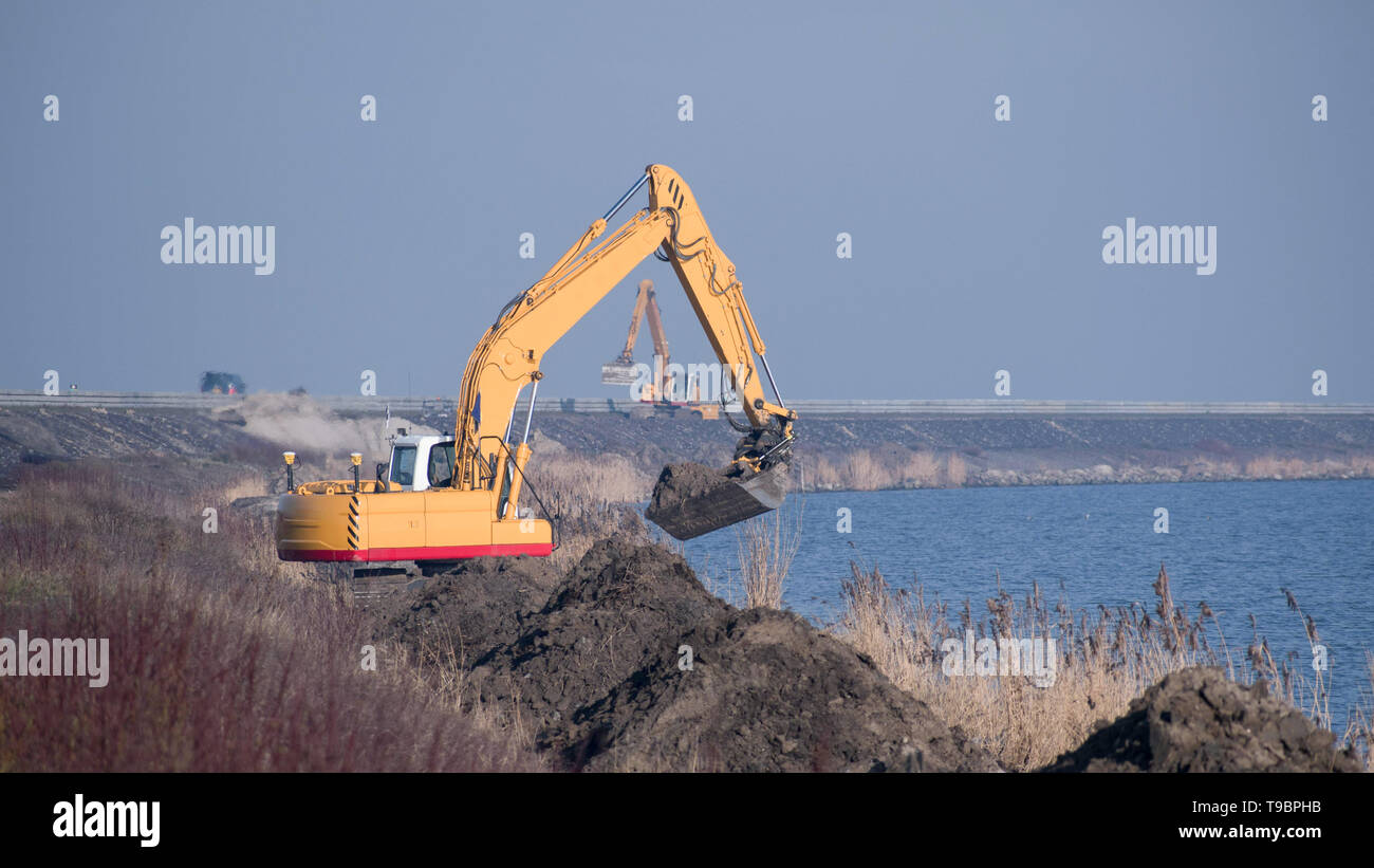 a yellow excavator at work at the line between land and water - Stock Image
