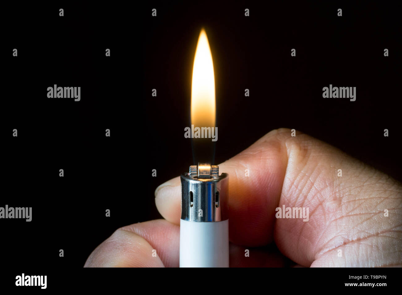 A hand lighting up a lighter with flame and dark background. - Stock Image