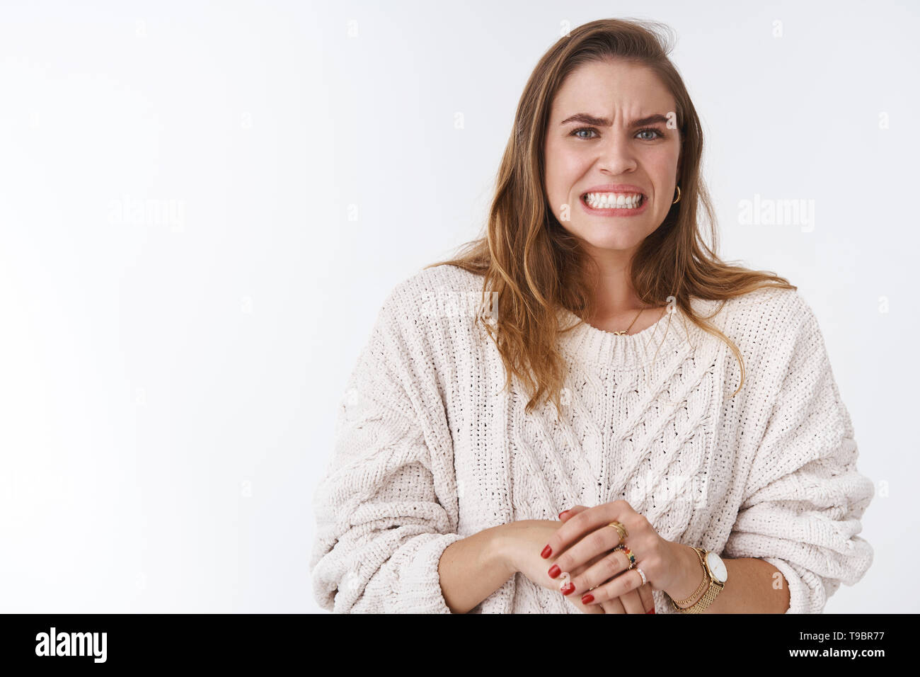 Woman feeling awkward intense feeling problems, making huge mistake worrying grimacing wrinkle nose clenching teeth stooping guilty, nervously - Stock Image