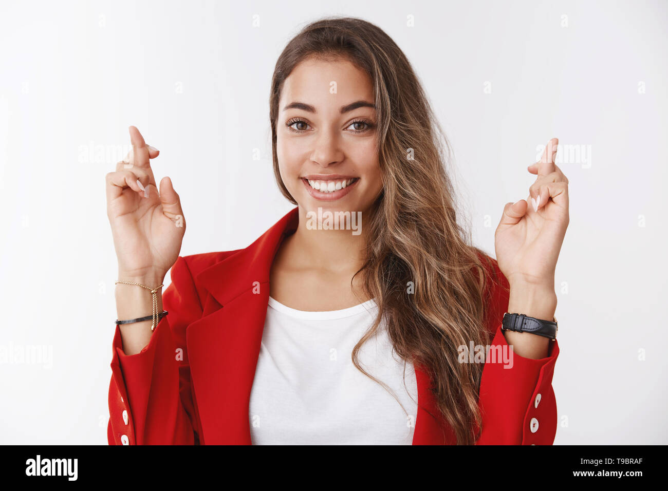 Optimistic happy woman making wish smiling aimed success, cross fingers good luck grinning looking camera hopeful excited, waiting positive results - Stock Image