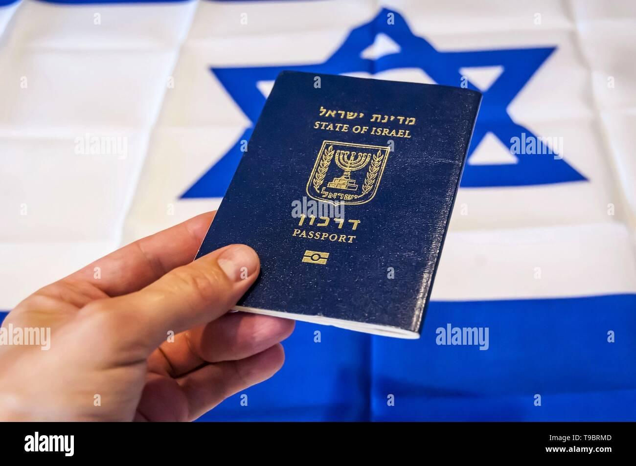 "Hand holding the passport of the State of Israel, Israeli flag on the background. Israel citizenship concept, Israeli biometric ""darkon"" passport Stock Photo"