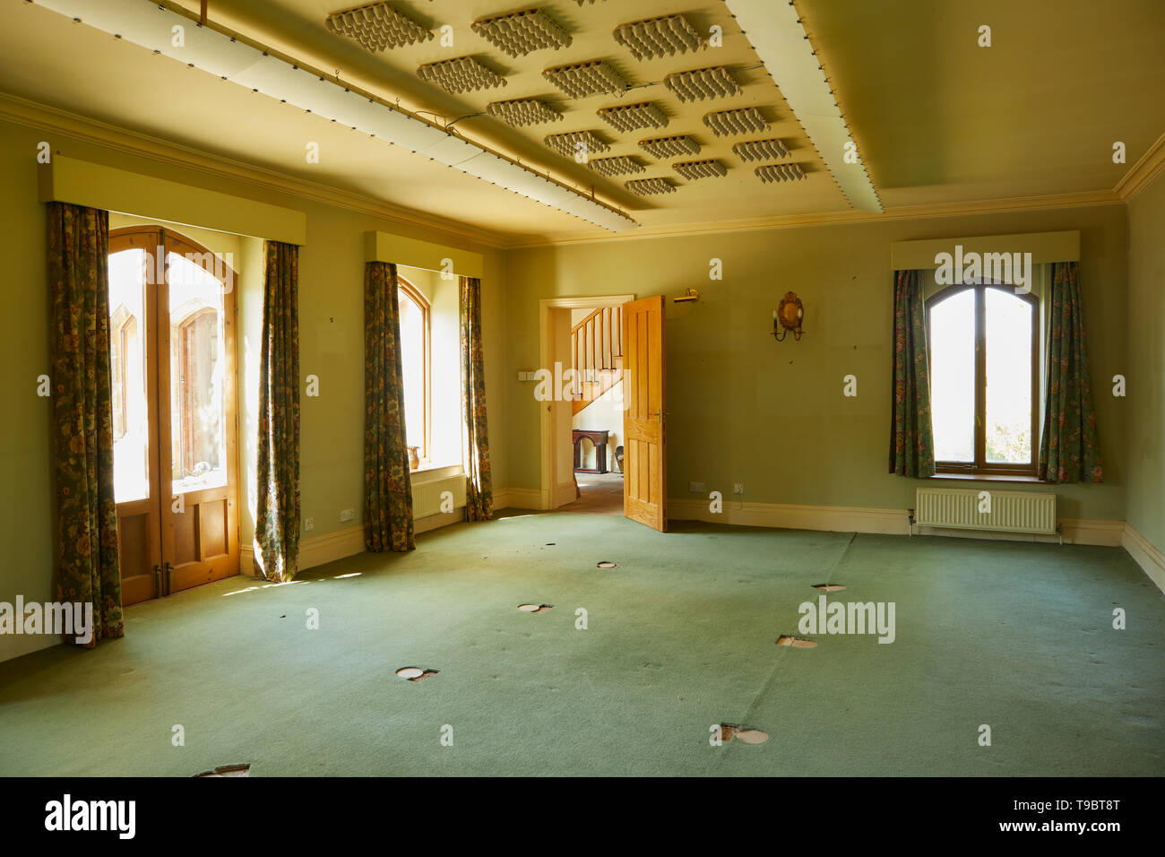 Once a billiard room a large carpeted empty area at the end of final house clearance. Sound deadening work to ceiling and flat lighting. Stock Photo