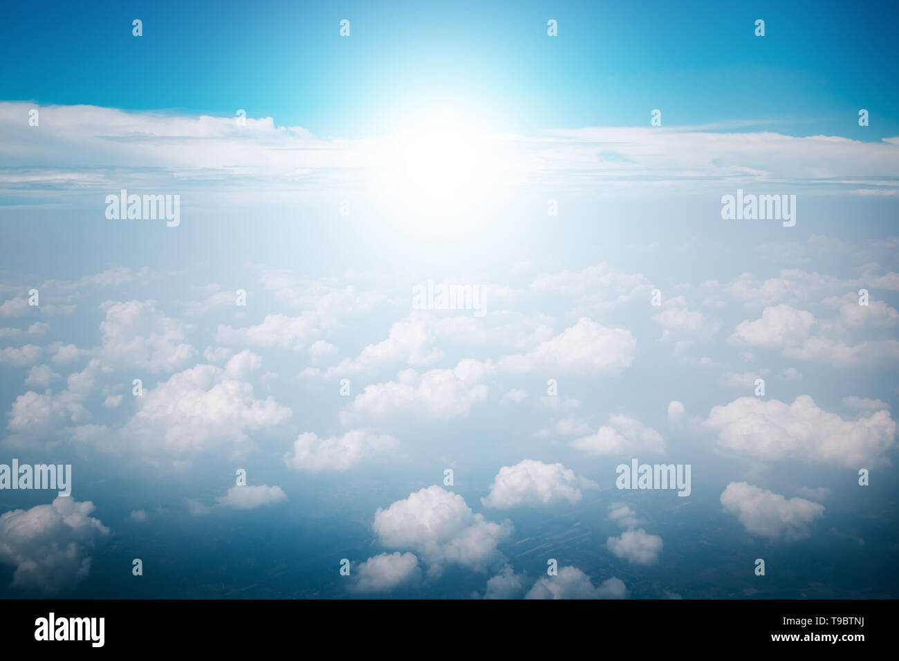 View of the sky clouds above the clouds from airplane window with sun light retro color filter Stock Photo