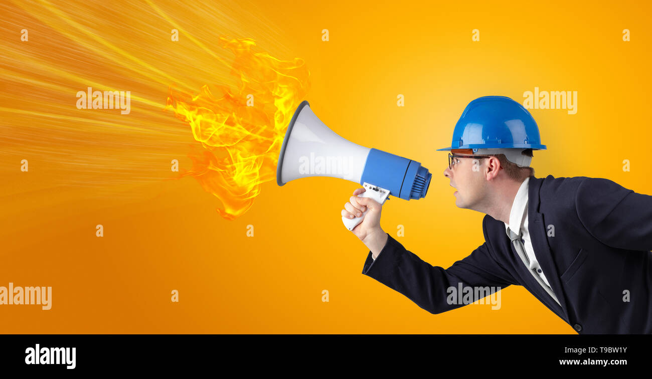 Young architect constructor yelling with megaphone with copyspace - Stock Image