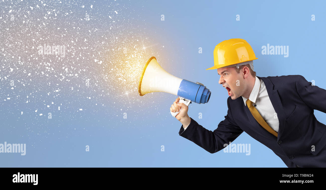 Young architect constructor yelling with megaphone and sparkling sounds  - Stock Image