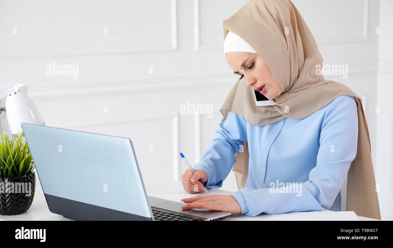 Young muslim woman in hijab is talking with client on mobile phone explaining situation, making paper notes and looking at laptop screen on her workplace in office. - Stock Image