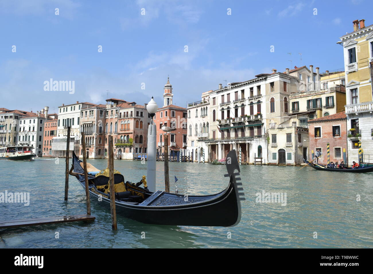 Venice/Italy - April 20, 2014: Beautiful gondola anchored at poles of the Grand canal in a sunny spring day. - Stock Image