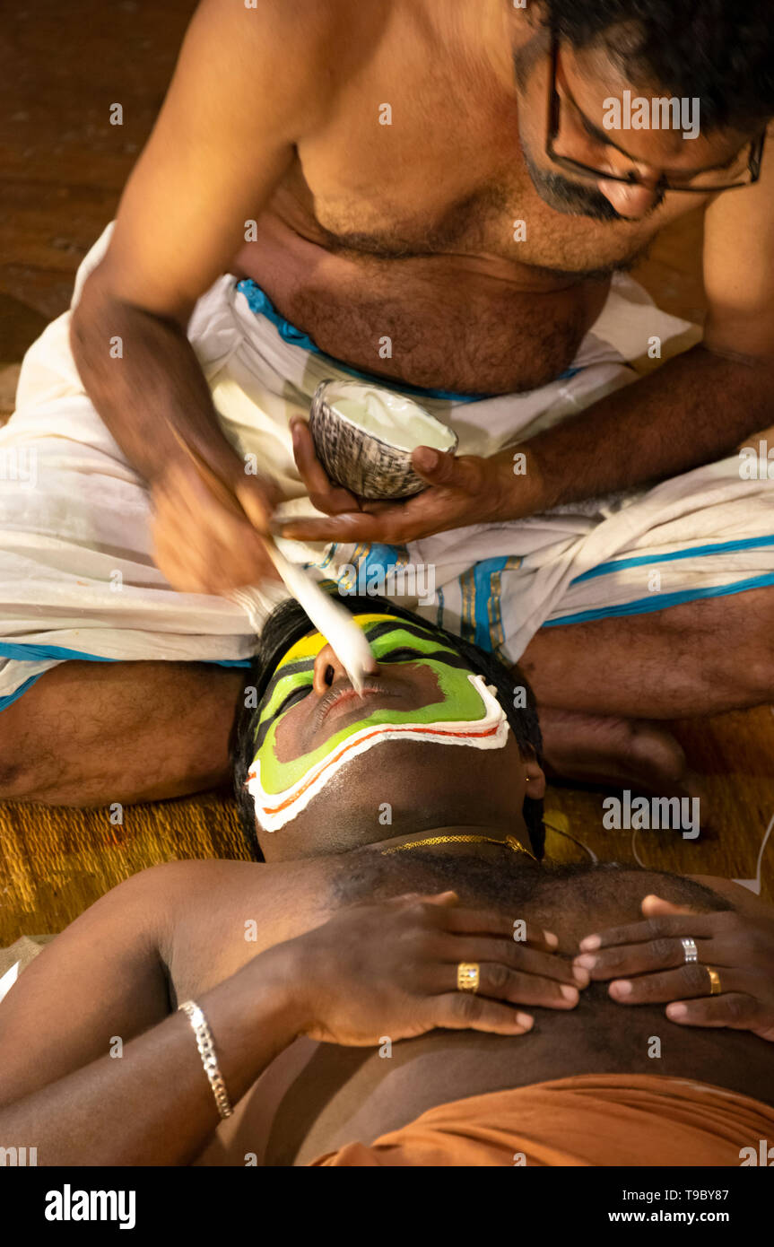 Vertical aerial view of the lead Kathakali performer having his distinctive make up applied in Kerala, India. Stock Photo