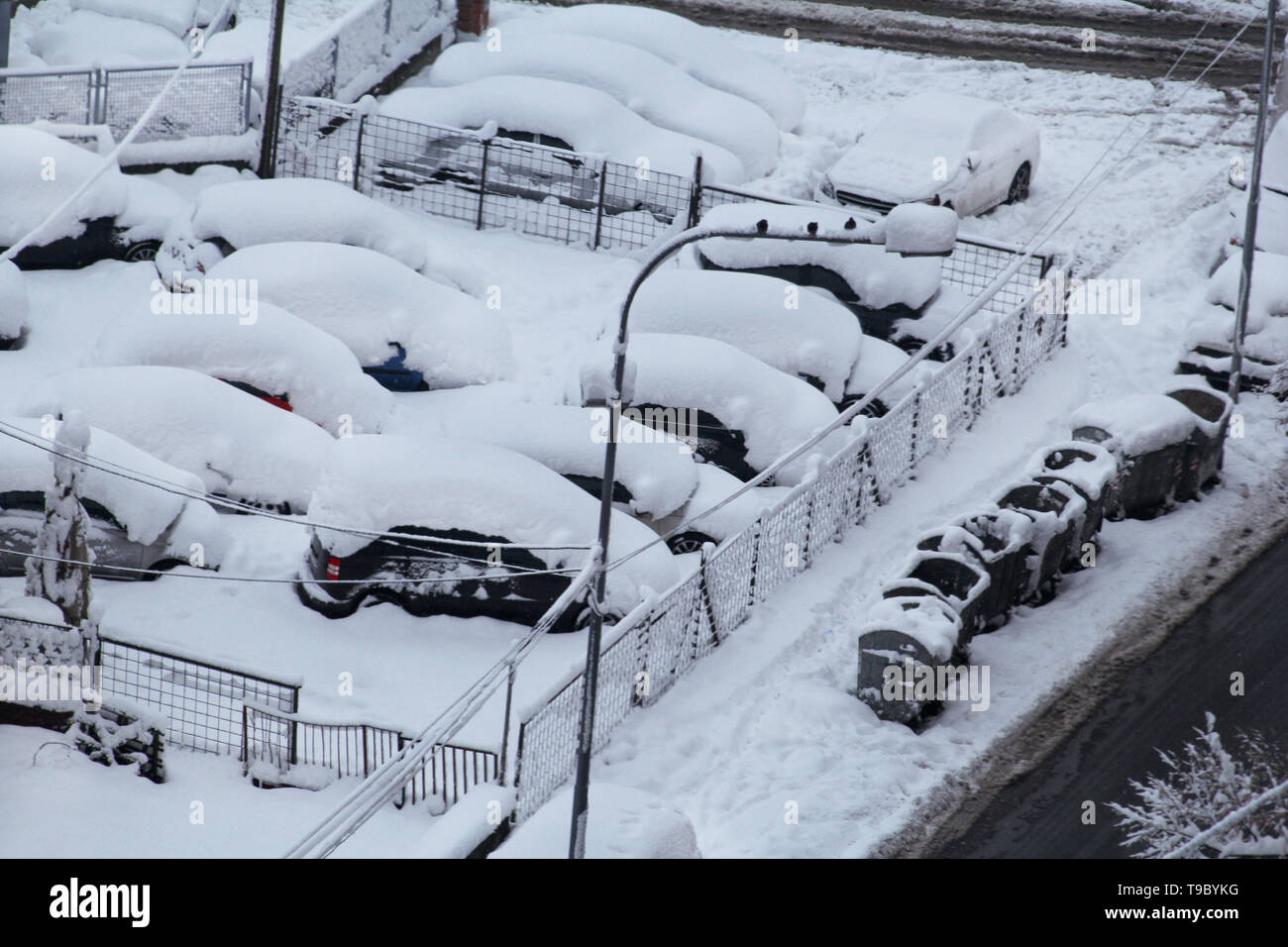 Cars on parking and street covered with big snow layer. View of winter and snowing on city street with snowflakes. In snowy season, motor vehicles. - Stock Image