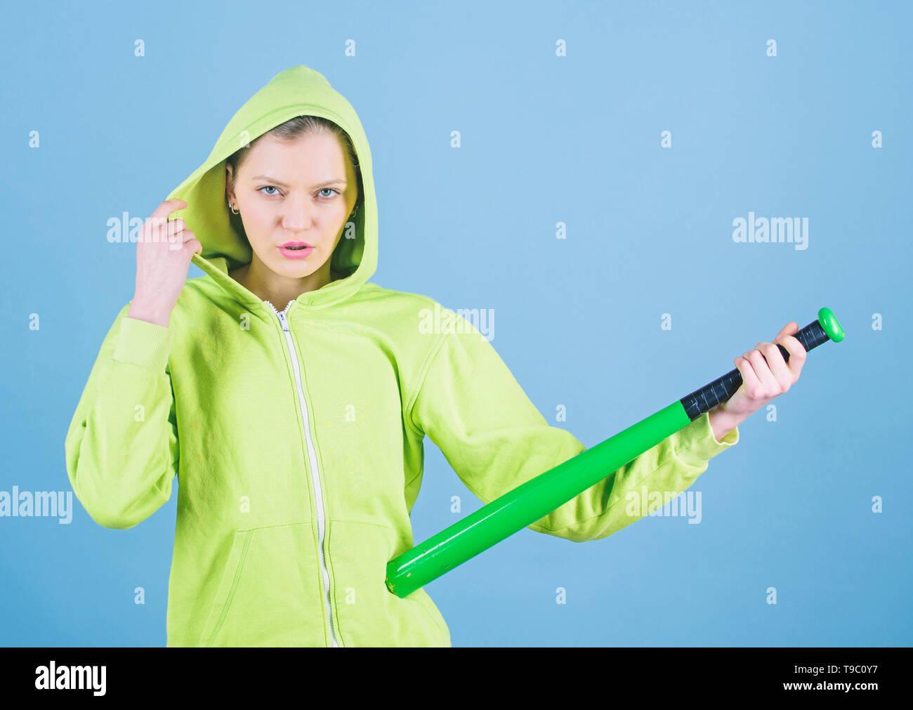 Feeling power. Woman play baseball game or going to beat someone. Girl hooded jacket hold baseball bat blue background. Woman in baseball sport. Baseball female player concept. She is dangerous. - Stock Image