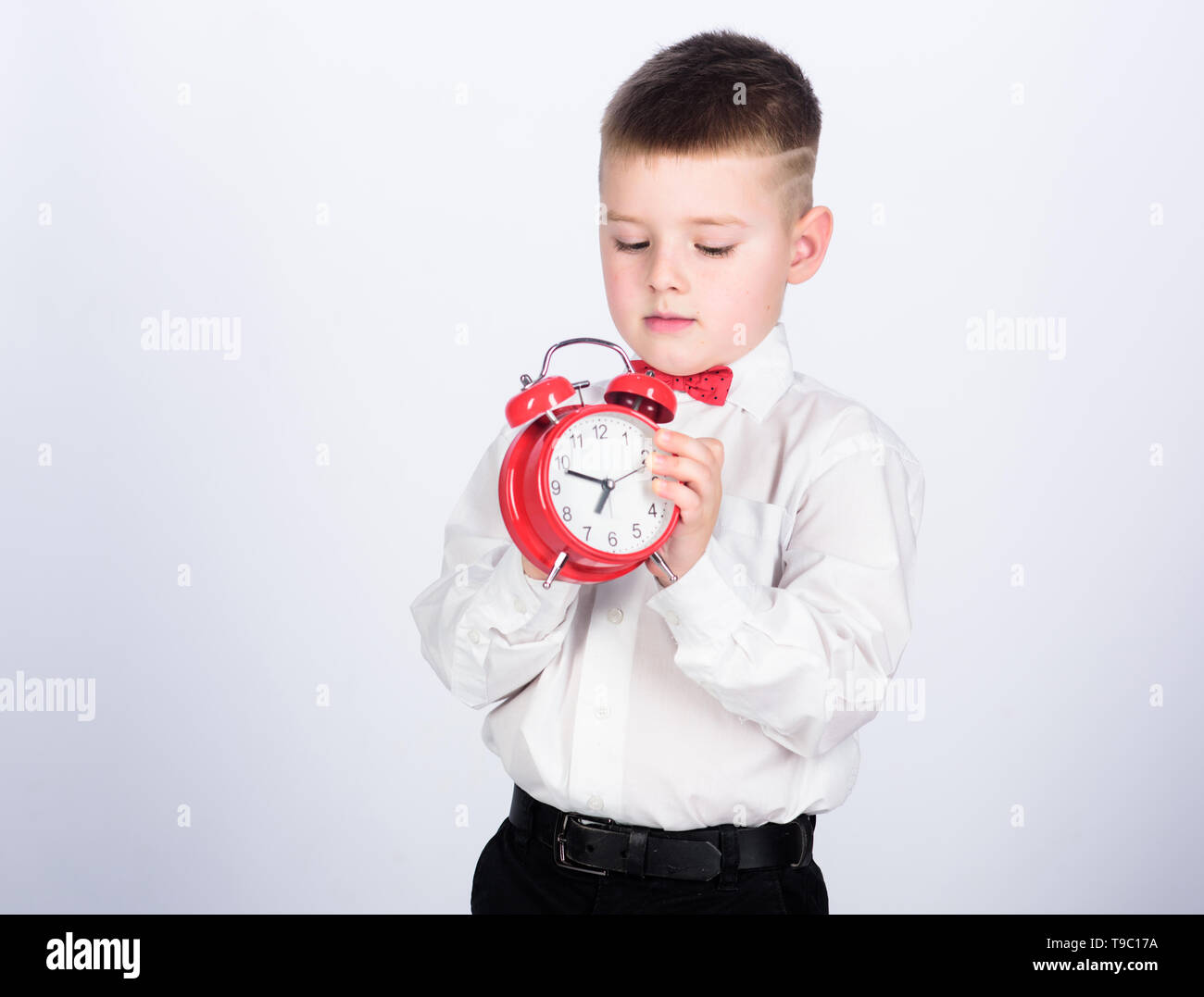 Set up alarm clock. Child little boy hold red clock. It is time. Schedule and timing. Morning routine. Schoolboy with alarm clock. Kid adorable boy white shirt red bow tie. Develop self discipline. - Stock Image