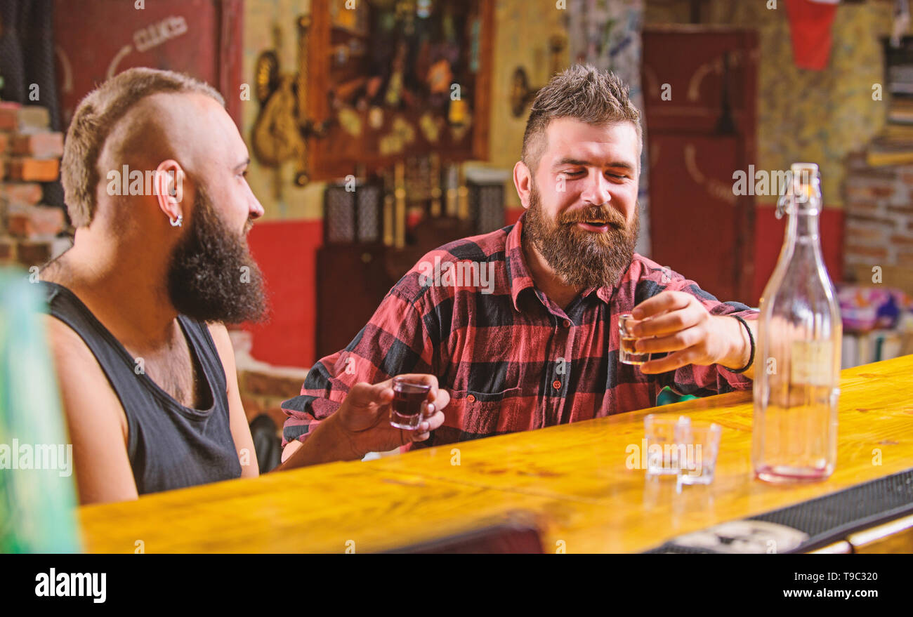 Friends relaxing in pub. Men drinking alcohol together. Alcohol addiction. Hipster brutal man drinking alcohol with friend at bar counter. Men drunk relaxing at pub having fun. Strong alcohol drinks. - Stock Image