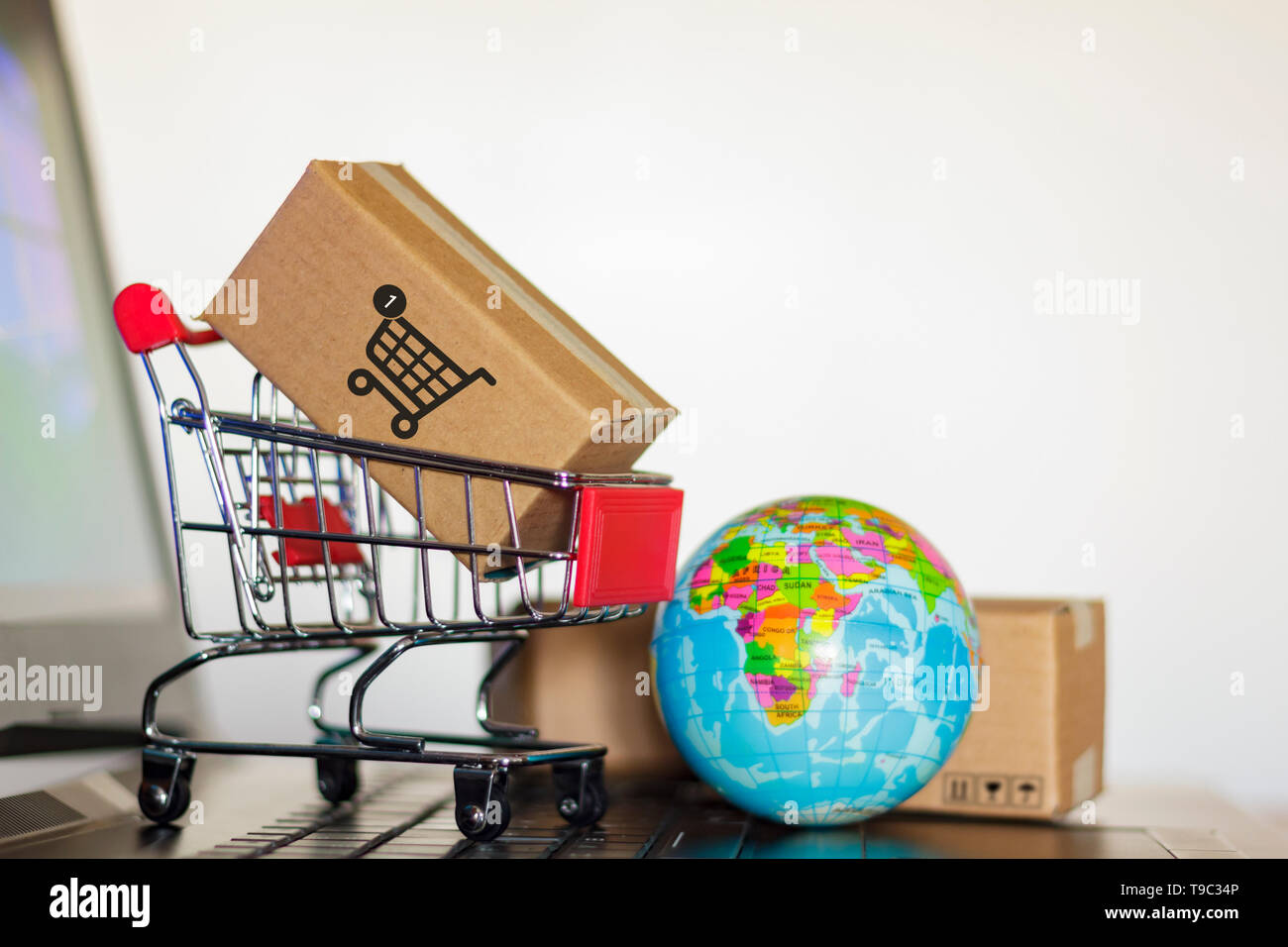 Trolley with boxes and earth globe on computer  Online