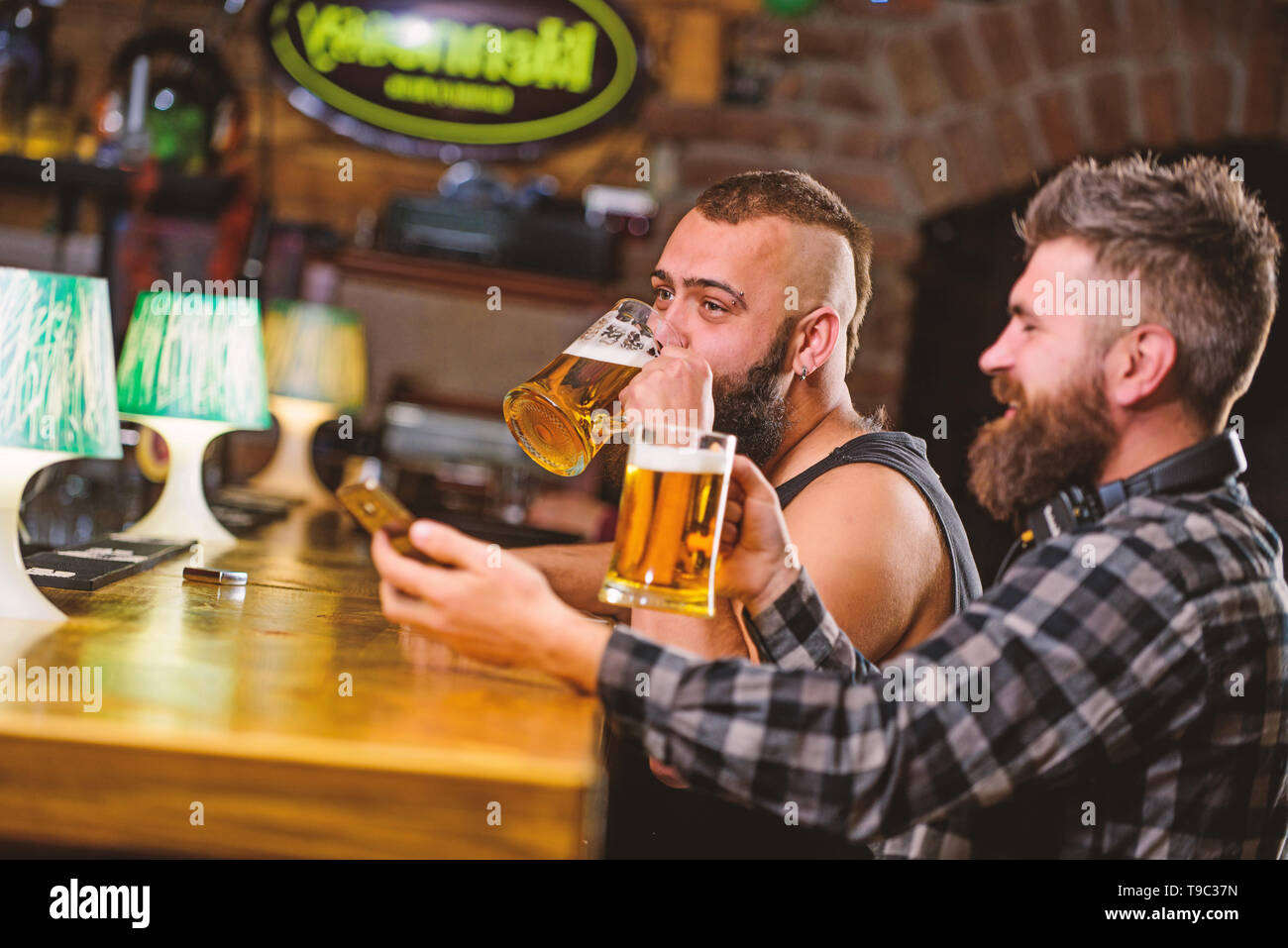 Men drinking beer together. Hipster brutal man drinking beer with friend at bar counter. Men drunk relaxing having fun. Alcohol drinks. Friends relaxing in pub with beer. Refreshing beer concept. - Stock Image