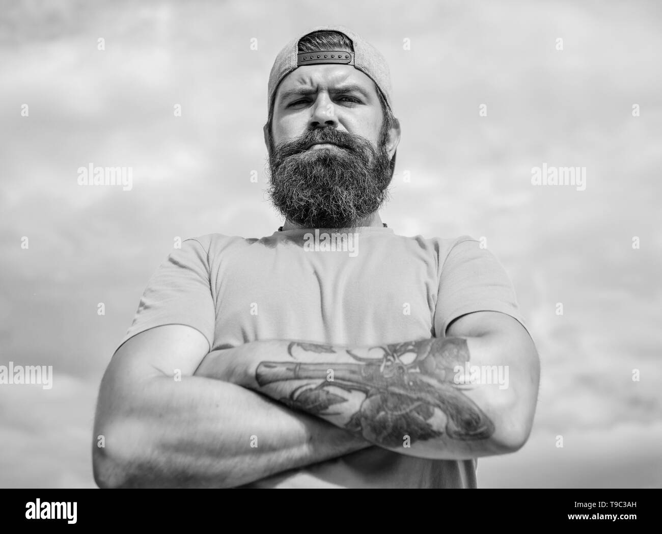 Too serious right now. Man bearded muscular brutal hipster outdoors sky background. Masculinity and brutality. Lumbersexual tattooed well groomed hipster. Hipster with mustache and long beard. - Stock Image