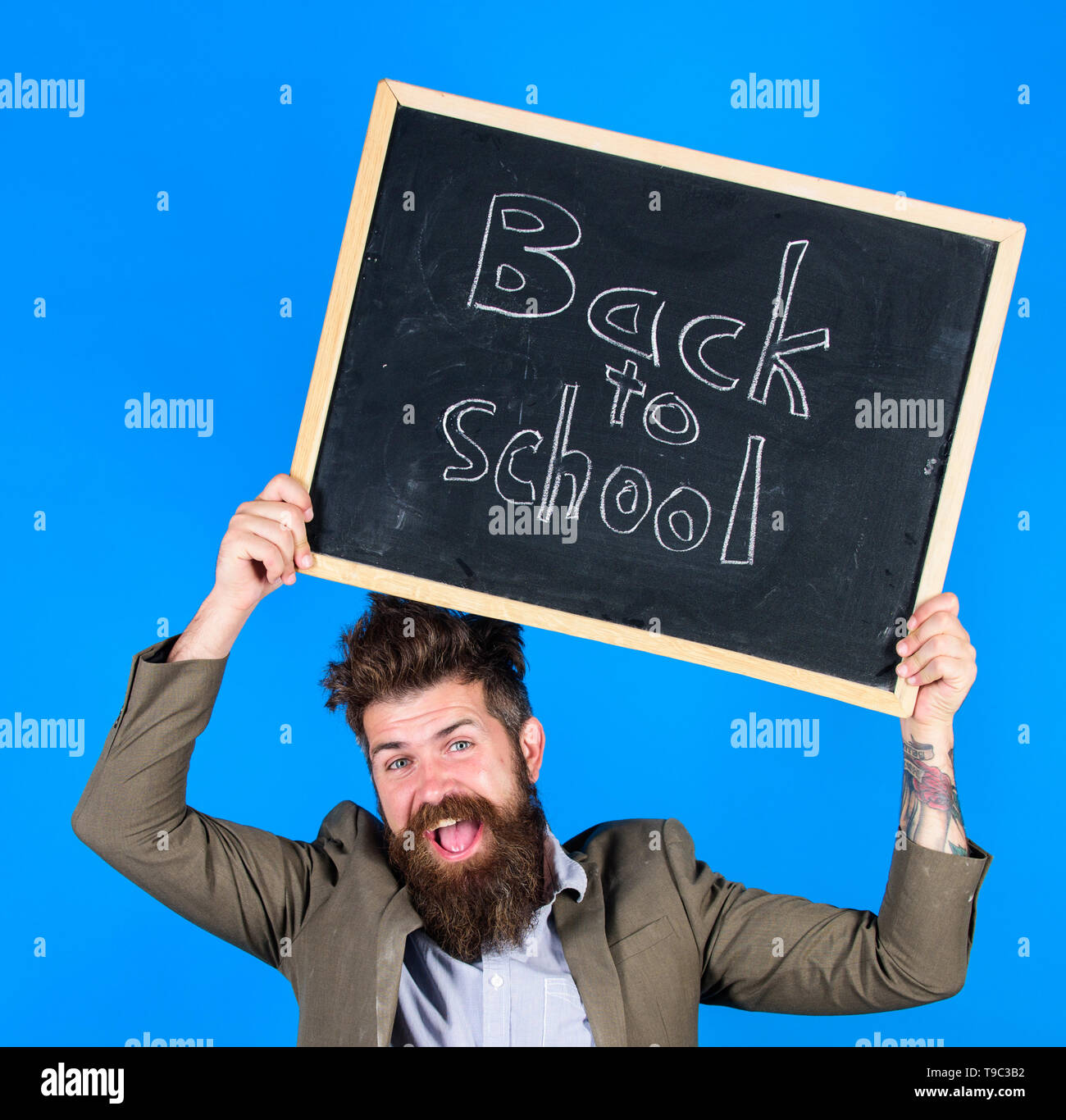 Stay positive. Teacher bearded man holds blackboard with inscription back to school blue background. Teacher with tousled hair cheerful about school year beginning. Keep working and be kind to people. Stock Photo