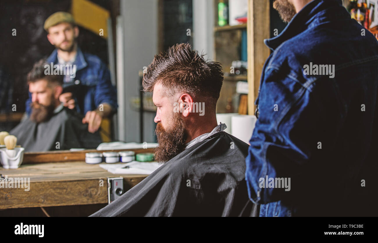 Barbershop concept. Man with beard covered with black cape sits in hairdressers chair, mirror background. Hipster with beard waits for barber and haircut. Man with beard client of hipster barbershop. - Stock Image