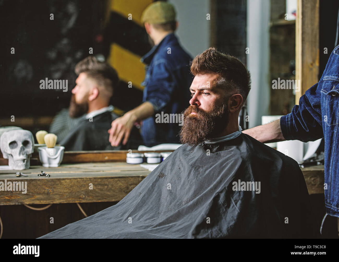 Man with beard covered with black cape sits in hairdressers chair, mirror background. Man with beard client of hipster barbershop. Barbershop concept. Hipster with beard waits for barber and haircut. - Stock Image