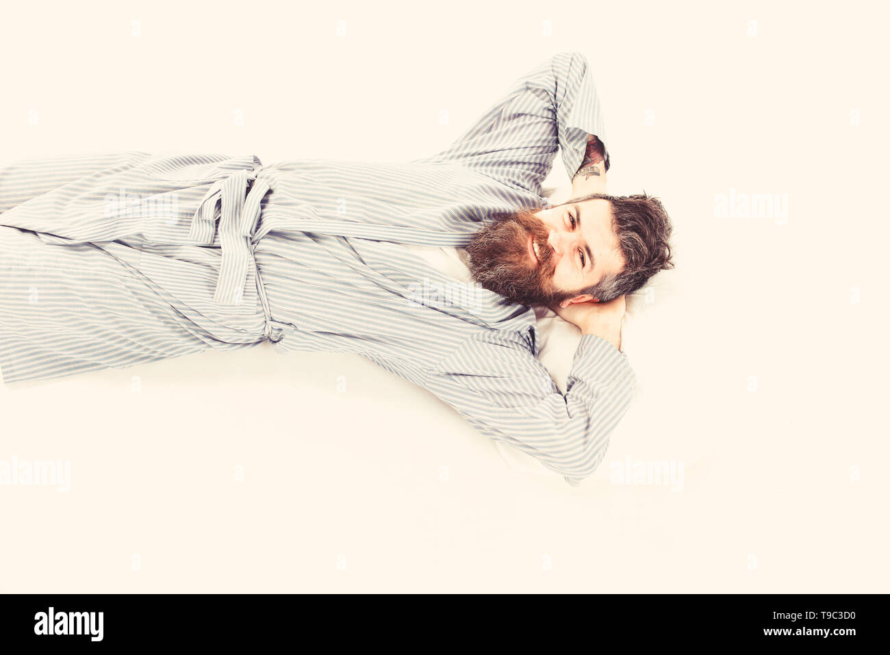 Slept well oncept. Man relax and having rest, white background. Man with smiling happy face wake up, lay on bed, put hands behind head, top view. Hipster with beard, mustache and messy hair slept well - Stock Image