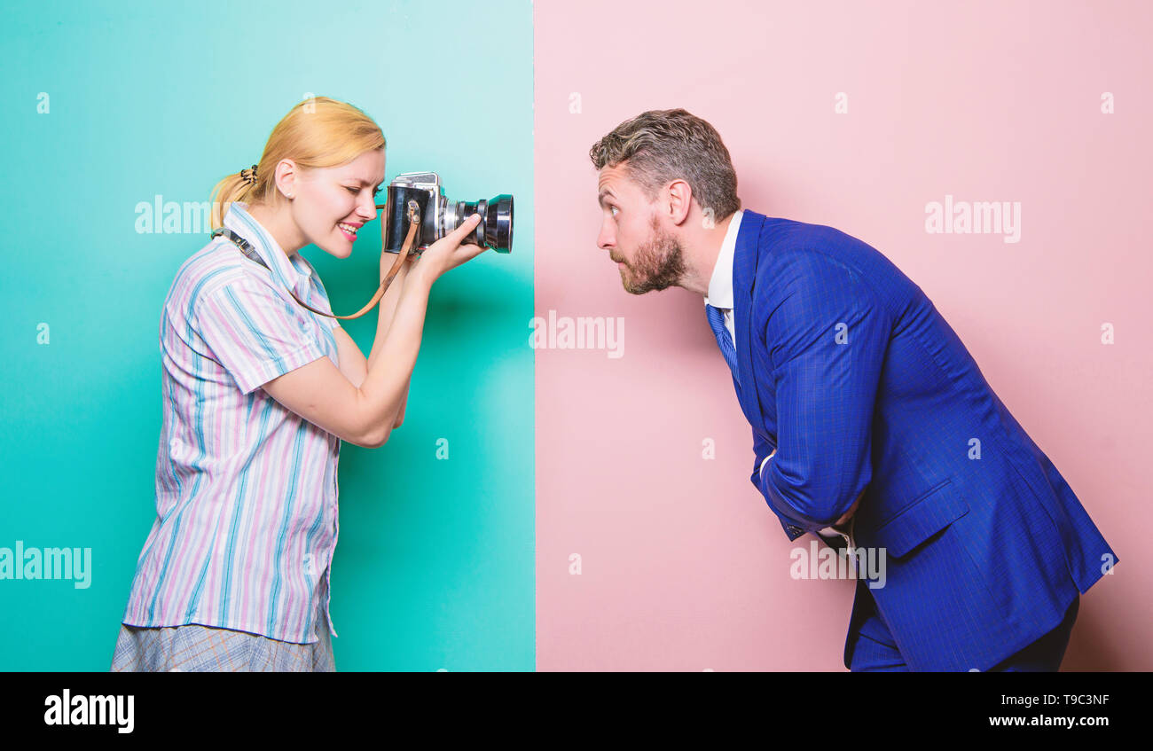 Creating a fashion look. Fashion shooting in photo studio. Businessman posing in front of female photographer. Photographer shooting male model in studio. Pretty woman using professional camera. - Stock Image
