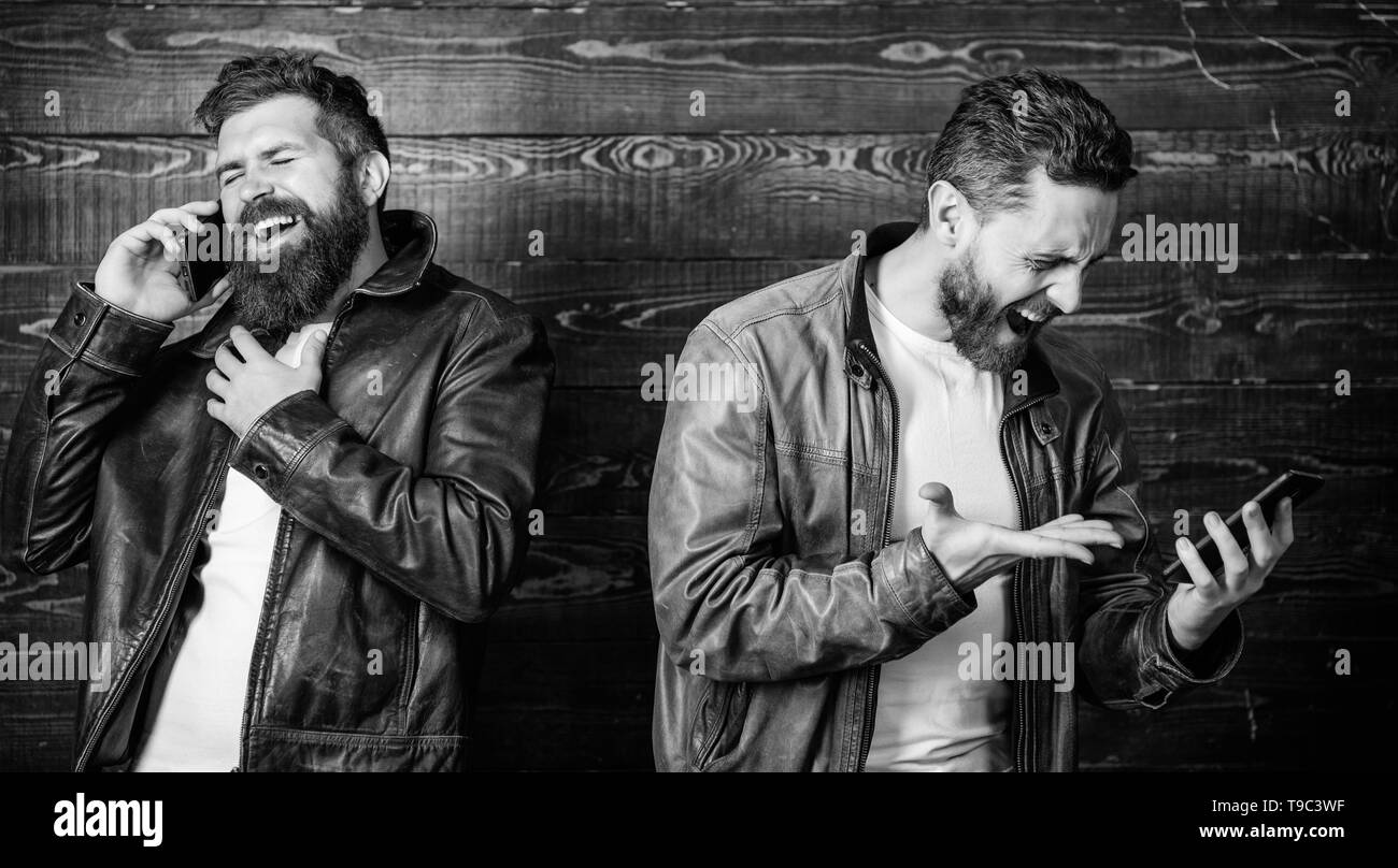 Mobile conversation and connect. Business call. Men brutal bearded hipster in fashionable leather jackets use mobile phone. Online business. Modern technology. Men with smartphones discuss business. - Stock Image