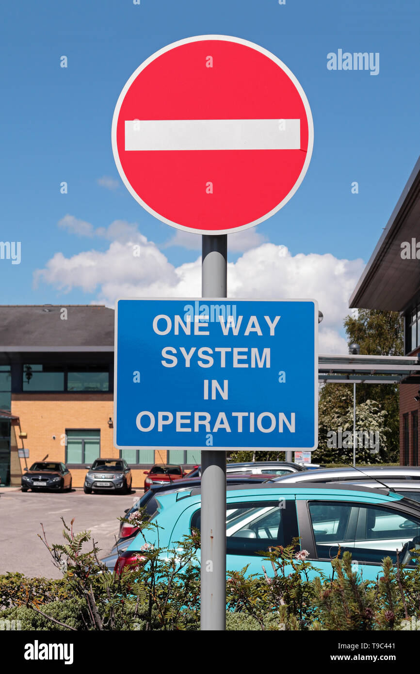 Bright Red and white 'No Entry' sign with white on blue 'One Way System in Operation' sign in an office car park - Stock Image