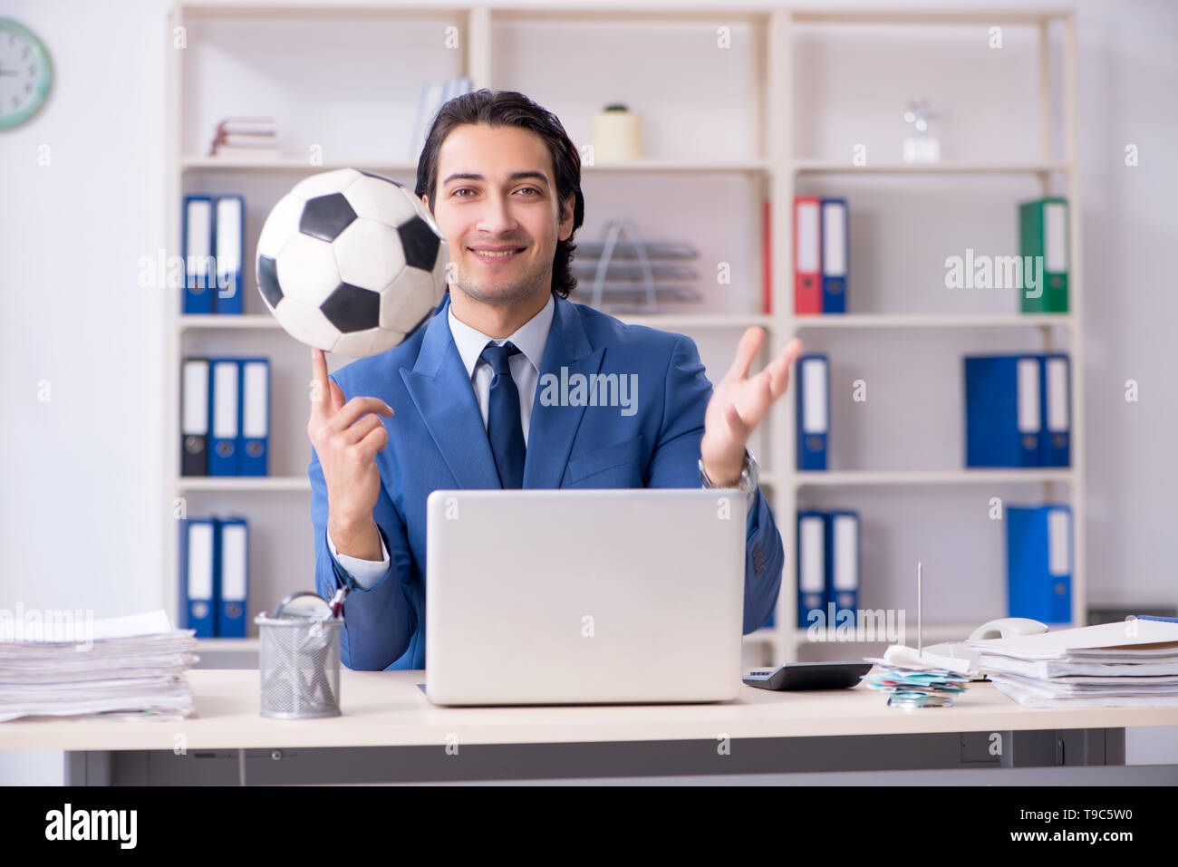 Young handsome businessman with soccer ball in the office - Stock Image