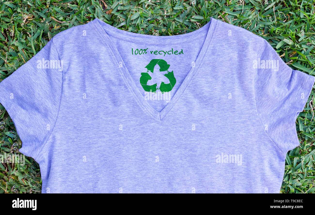 Recycle clothes icon on t shirt with 100% Recycled text, concept illustration reuse, recycle clothes and textiles to reduce waste - Stock Image