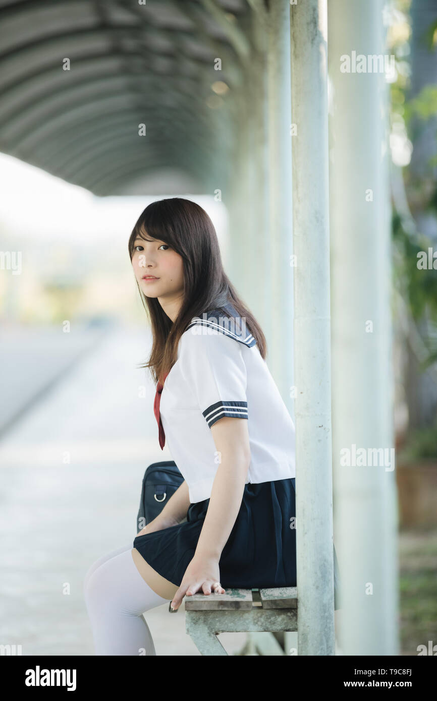 710dba856 Portrait of asian japanese school girl costume sitting and looking at park  outdoor - Stock Image