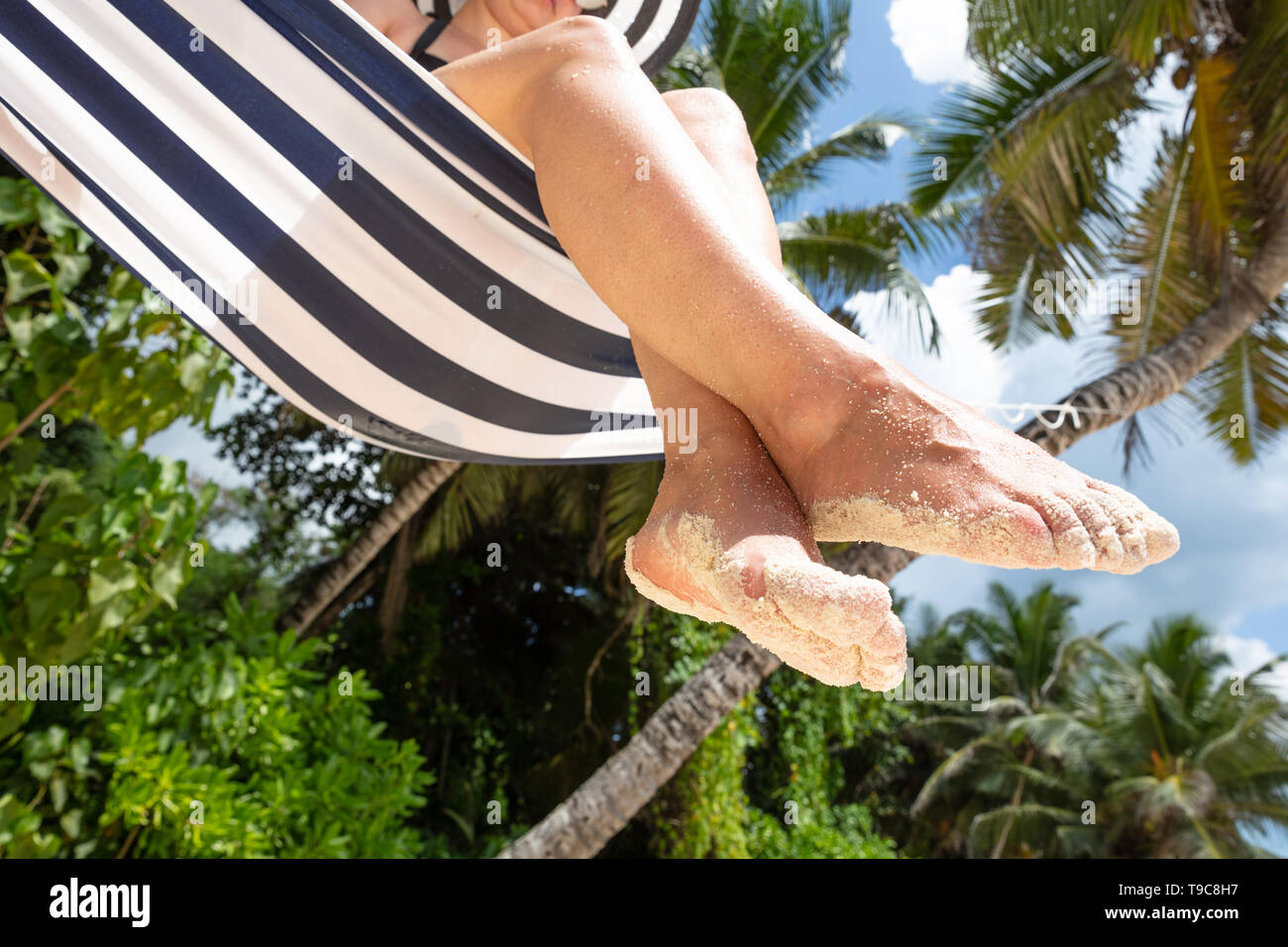 Low Angle View Of Sand On Woman's Feet Sitting On Hammock At Beach - Stock Image