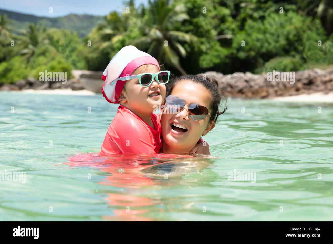 Close-up Of Mother And Daughter Wearing Sunglasses Swimming In The Sea - Stock Image