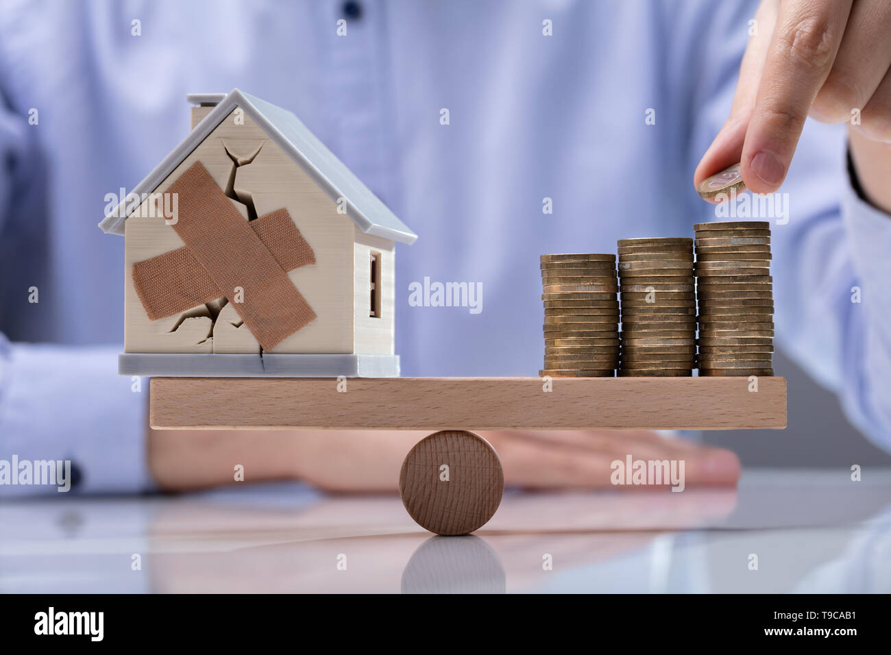 Man's Hand Placing Coin On Top Of The Stack Coins And Broken House Over Seesaw - Stock Image