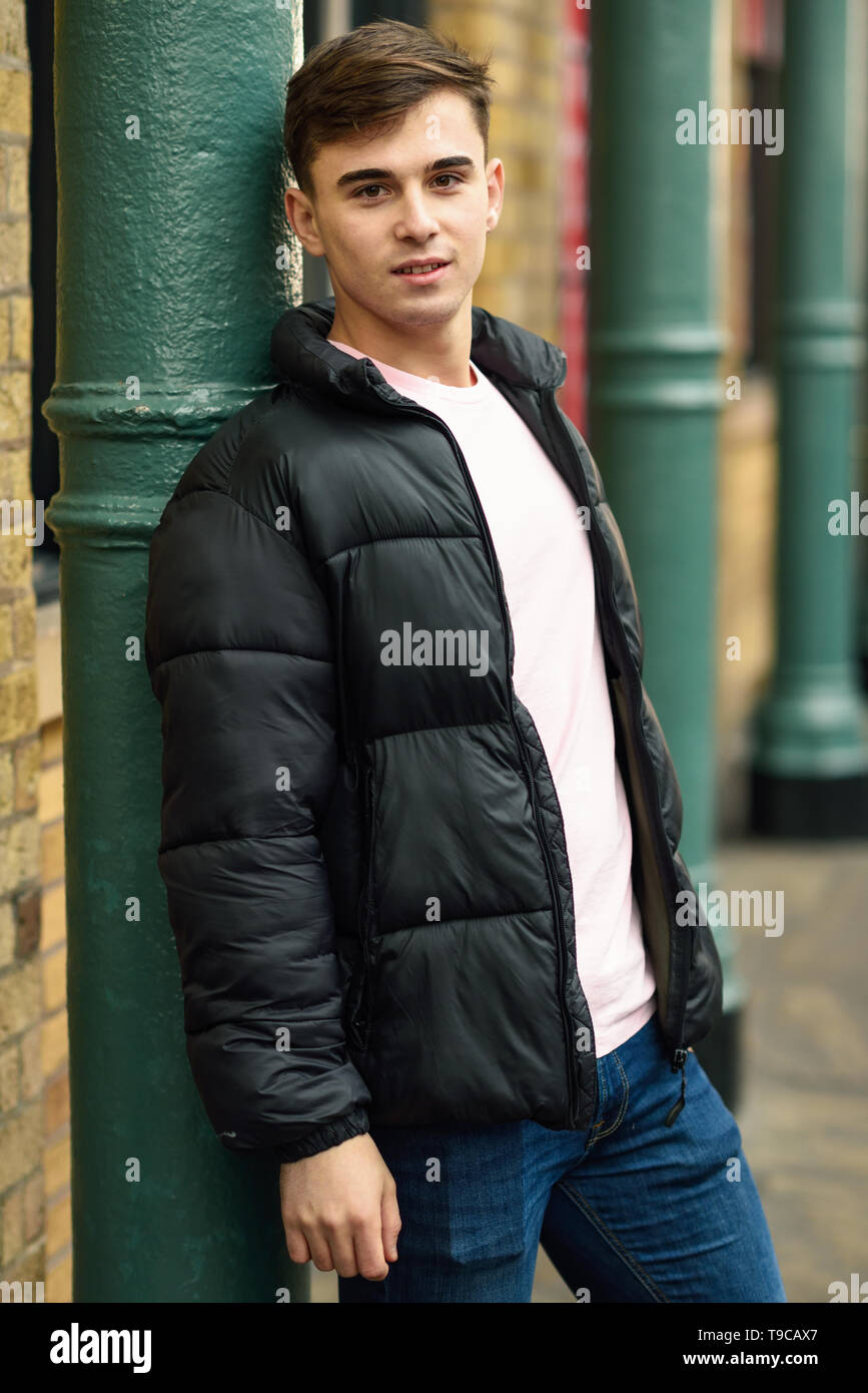 Young man standing in urban background with modern hairstyle. London, UK. - Stock Image