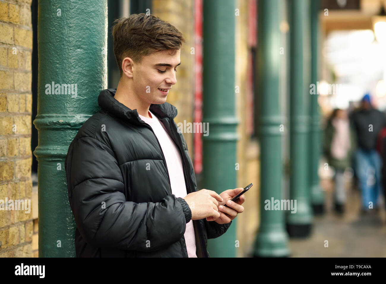 Young urban man using smartphone in urban background in London, UK - Stock Image