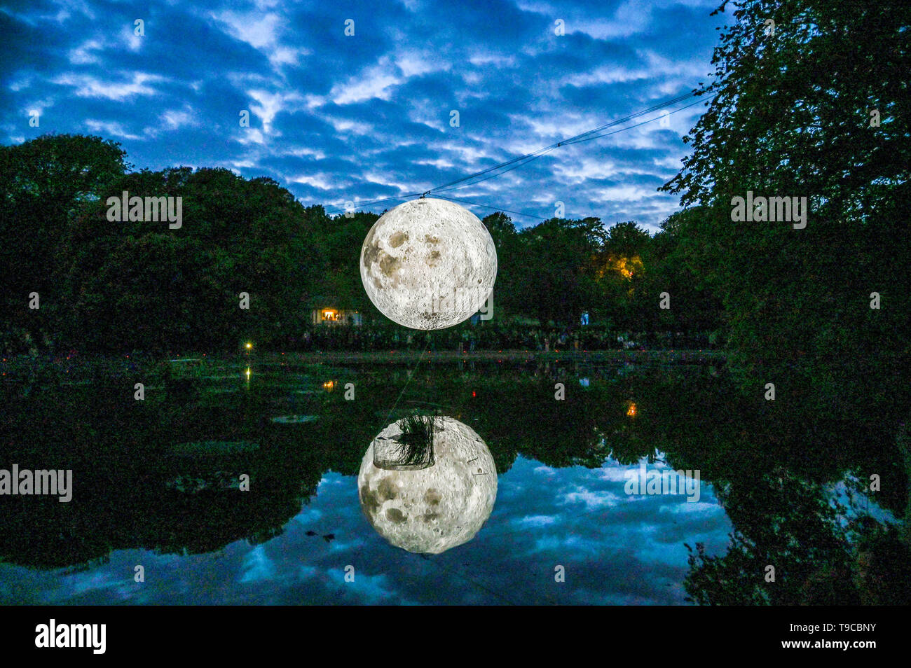 Brighton UK 30th April 2019 - Crowds gathered around Queens Park pond in Brighton this evening to watch the Brighton Festival event 'Museum of the Moon' by artist Luke Jerram . The moon will be lit up over the weekend accompanied by music by composer Dan Jones . - Stock Image